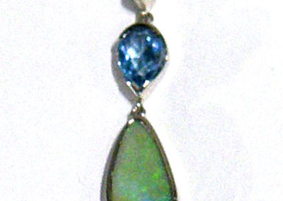 Joan Thomson, Blue Green Pendant: Peridot blue topaz, opal in matrix, white gold; bezel set stones, piercing. 2012, NFS.