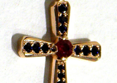 Joan Thomson, Ruby Sapphire Cross: Ruby, sapphire, 14k gold; lost wax casting, bead set sapphires, modified bezel setting. 2013, $2,660.