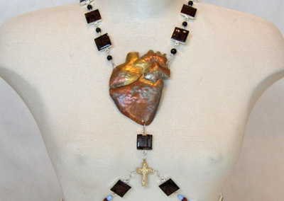 My Heart's Foundation, Gail Daggett, 2010/11, Copper, silver plated brass, sterling silver, clear doming resin, tin, black onyx, wood, tar paper from my grandmother's house, wood and blue plastic beads from my grandmother's rosaries & 10k gold