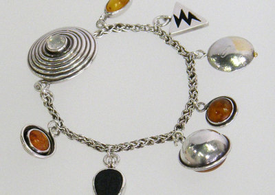 Charm (Megan Broner), 1991: Fine silver, 22k gold, 18k gold, Baltic amber, black onyk, trilobite (fossil), sterling silver, moonstone; Handmade chain, construction, reticulation. NFS