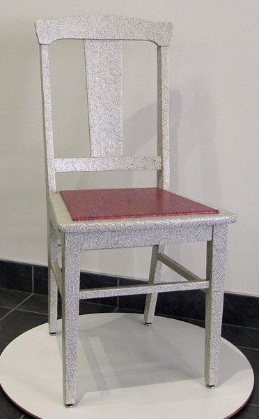 Seat of Higher Learning (Cathryn Miller), 2011: Maple chair; pages from Volume 1, Universal Standard Encyclopedia, Deluxe Edition; fir plywood; arcival inkjet print on Arches text, polyacrylic varnish. $400