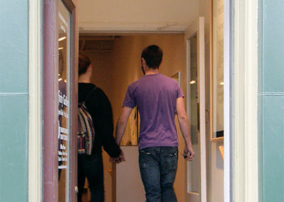 Couple entering gallery reception hand-in-hand.