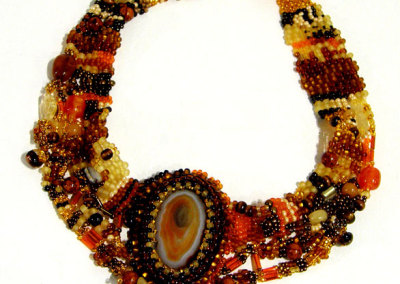 Lynne Cornish-Braun, Ancient Skies: Seed beads, agate stone, glass beads, stone chips, vintage button; peyote (free form), bead embroidery, brick stitch, picot. 2012, $325.