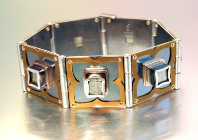 "HINGED PYRITE CUBE BRACELET. Sterling silver, 14k yellow gold, iron pyrite, anodized titanium, patina. Selected for ""Dimensions 2011"", Merit Award. ""Form – Four Regina Jewellery Artists"" Exhibition, Affinity Gallery."