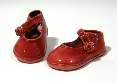 Red Patent Mary Janes-Infant, 3-6 months (Judy Tryon), 2014: Clay, underglaze, fabric, glue; slabs cut and fitted; fabric post-firing, electric fired cone 4. $150
