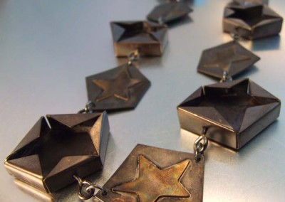 CHARRED STAR CHAIN – Melody Armstrong, 2014, copper, sterling silver, fabricated, soldered, scoring and bending, oxidized, 31 x 3.6 x .9 cm.  $1250