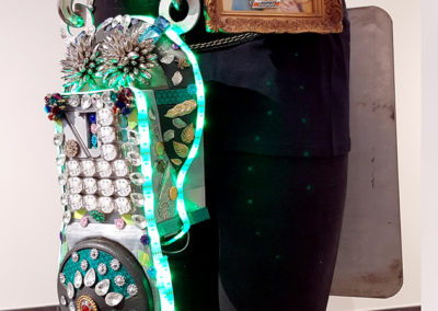 3 Hour Max (Jennilee Cardinal-Schultz, Saskatoon, SK), 2017: Ethically sourced parking meter and parking sign, LED strip lighting, motion detection LED lights, discarded bijoux and trinkets; welding, gluing, collaging. $600. 2nd Place Winner – Codpiece.