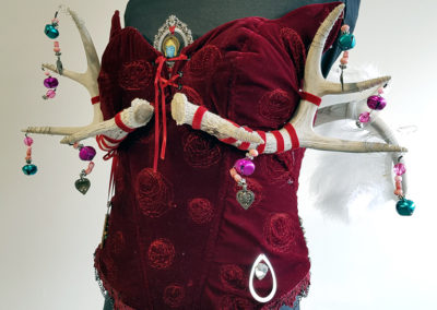 Sensual Animal Sweet Angel (Kim Hubar, High Prairie, AB), 2017: Deer antlers, feathers, beads, wire, metal plates, velvet and cotton fabric, ribbon, chain, charms; hand sewing, maching sewing, gluing. $250.