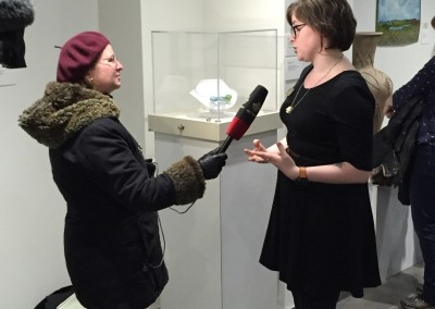 Exhibitions Coordinator Maia Stark speaks with a reporter from CBC Saskatoon.