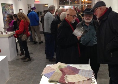 Reception guests read a Dimensions catalogue in Affinity Gallery during the Opening Reception.