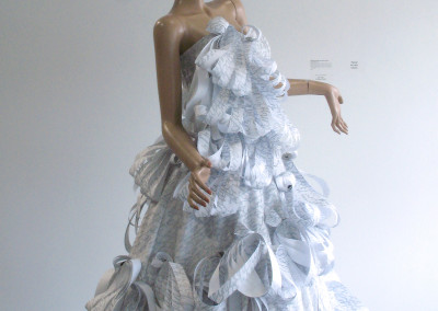 Paper Princess (Monique Martin and Janet Taylor): Fabric (taffeta, cotton, polyester, tulle), gros-grain ribbon, zipper, grommets, boning, thread, hook and eyes, paper (print run ends from a print shop), ink, safety pins, plastic zip ties, re-purposed jewelry and buttons. $700.