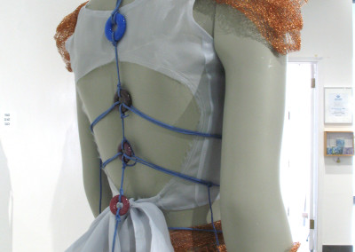 Strong…like a girl (Elizabeth Miller, Bob Miller, and Kelsey Murphy): Woven material, nylon thread, copper netting, coloured sheet glass, colour glass powder, colour glass frit (crushed glass), dichoric glass, faux leather cording, metal bails. Not for sale.
