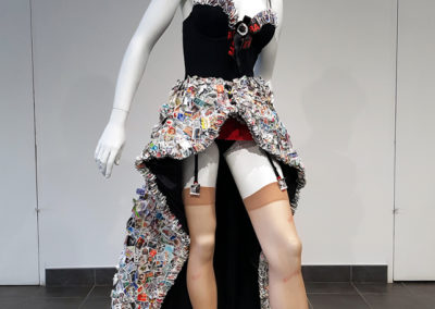 Postmistress (Monique Martin, Saskatoon, SK), 2017: Approximately 11,000 used postage stamps from around the world, chiffon, beads, sequins, lycra, buttons, thread, cardboard, glue, ink, nylons, ribbon, boots, venetian blind hardware; collage, machine sewn, hand stitched. $1,700. Best in Show.