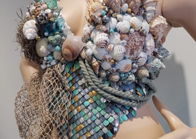 The MerWitch (Tess Schlosser, Saskatoon, SK), 2017: satin, tulle, beads, pearls, seashells, rocks, sea glass, metal scales, hemp netting, rope, jewelry chain, moss; sewing, hand-knotting, scale maille, gluing. $750. 2nd Place Winner – Open.