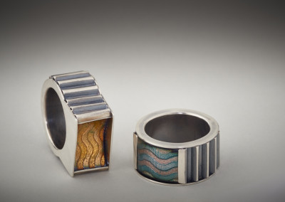 "Melody Armstrong (Regina) ""Corrugated Wave Rings"", 2015; Sterling silver, enamel on etched copper; soldering, etching, enamelling, corrugating, setting; Taller: 2.8 x 2.5 x 1.2; Shorter: 2.4 x 2.4 x 1.3; Value: $1,325.00; For Sale"