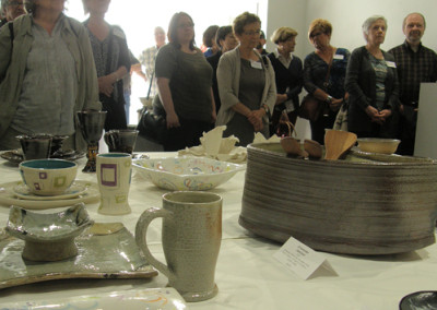 Guests standing around the display of table settings listening to opening remarks