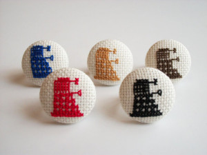 Daleks from the BBC show Dr. Who in cross-stitched ring form. Source.