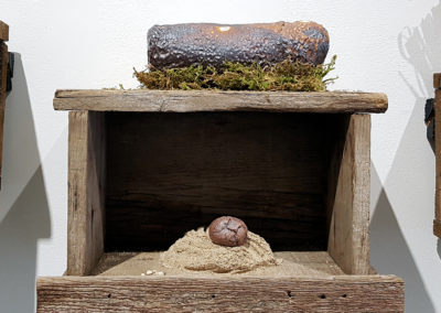 Primordial Being/Etre primordial (Claude A Morin), 2016: Stoneware clay, porcelain, glazes, oxides, moss, aged wood; thrown, salt, and gas fired glazed pieces, woodwork and textured sand. 28 x 33 x 17.5 cm. $400