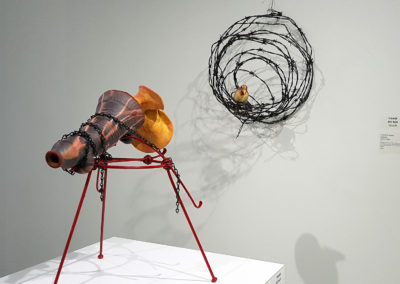 Ear to the Ground/À l'écoute (Claude A Morin), 2017: Stoneware clay, porcelain, glazes, oxides, wire, steel, paint; gas fired handmade and thrown clay, spiraled wire nest and steel support. wall: 59 x 47 x 36 cm, pedestal: 50 x 35 x 36 cm. $1000
