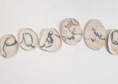 17. Plate Series 1-10 (Japneet Kaur, Ontario), 2019: Mid-fire porcelain, underglazes, underglaze pencils, glaze;hand molded, hand painted. Installation size: 34 x 176 x 1.   $1300