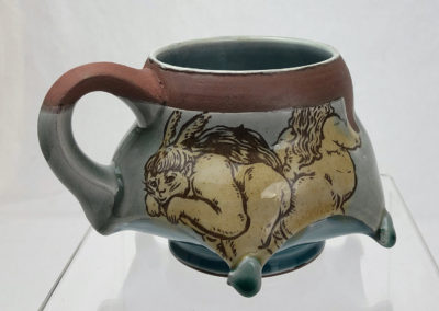18. Eyes Spies Mug (Shaun Mallonga, Ontario), 2018: Red stoneware, slip, glaze; wheel thrown, altered, sgraffito, glaze trailing. 8 x 13 x 12. $80