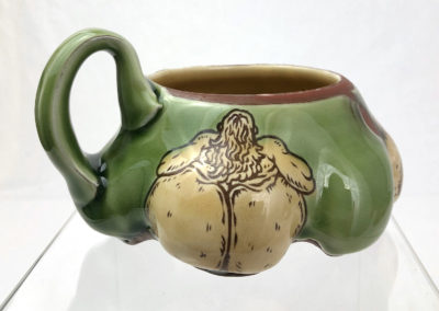 21. Green Onion Butt Mug (Shaun Mallonga, Ontario), 2018: Red stoneware, slip, glaze; wheel thrown, altered, sgraffito, glaze trailing. 9.5 x 16 x 15. $80