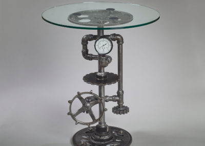 2. Sprocket (James Cathcart), 2019: Cogs and gears from vintage equipment, transmission parts, tempered glass; welded, polished, clear coat, gun oil bluing. 73.5 x 61 x 61. $2000