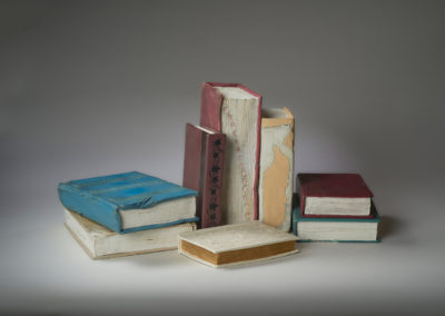 32. Found in the Attic (Lorraine Sutter), 2019: Porcelain, underglaze, acrylic, dirt; slab-built. Eight pieces, sizes variable-largest book: 25.5 x 19.5 x 7.5; smallest book: 16.75 x 11.5 x 3. $900. Award for Excellence in Fine Craft.