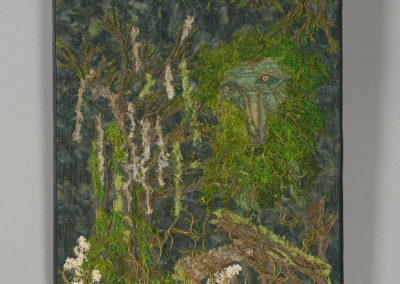 7. Greenman -- The Keeper of the Forest (Carol Ewles), 2018: Batik, natural moss, cedar branches, lichens, bark, vines, puff paint; quilted, couched, thread painted. 51 x 40.5 x 2. $475 NFS.
